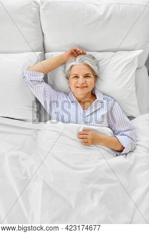 sleeping, old age and people concept - happy smiling awake senior woman lying in bed at home bedroom