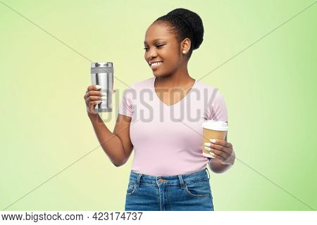 sustainability and people concept - portrait of happy smiling young african american woman with coffee cup and tumbler for hot drinks over green background