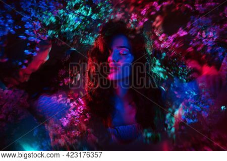 A Fantastic Shot Of A Girl In Flowers With Neon Multicolored Light And Phantasmagoria. The Concept O