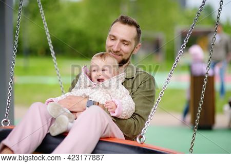 Toddler Girl Having Fun On Outdoor Playground. Young Father Rides Daughter On Swing. Spring/summer/a