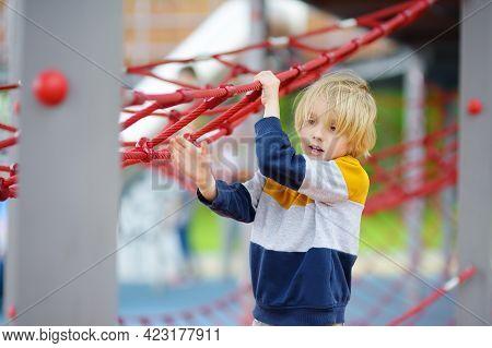 Cute Preschooler Boy Having Fun On Outdoor Playground. Spring/summer/autumn Active Sport Leisure For