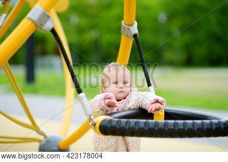 Cute Toddler Baby Having Fun On Outdoor Playground. Adorable Little Girl Is Swinging. Kindergarten,
