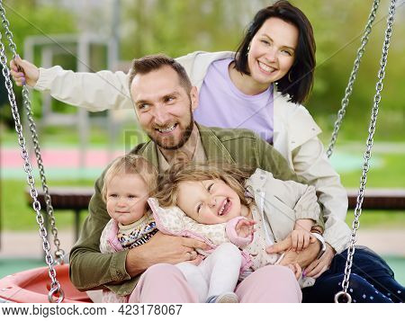Merry Family With Two Children Having Fun On Outdoor Playground. Young Parents Rides Daughters On Sw