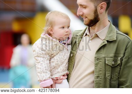 Cute Toddler Girl Having Fun On Outdoor Playground. Young Father Playing With His Little Daughter. S