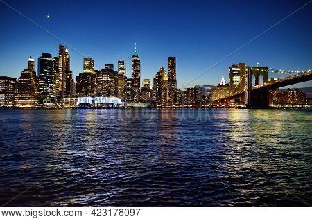 Skyscrapers Of Manhattan And Brooklyn Bridge At Dusk. Famous Bridge. Postcard View Of New York. Unit