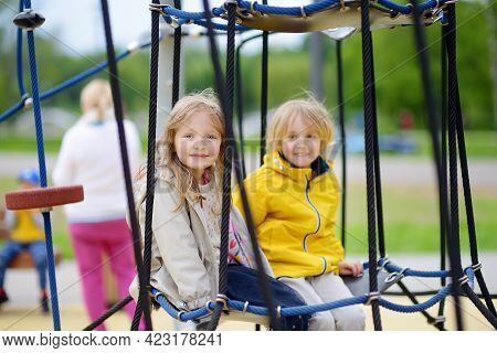 Two Children Having Fun On Playground. Spring/summer/autumn Active Sport Leisure For Kids. Outdoor A
