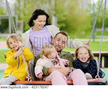 Merry Family With Three Little Children Having Fun On Outdoor Playground. Young Parents Rides Daught