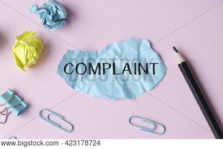 Text Complaints In Paper On Pink Table With Office Tools.