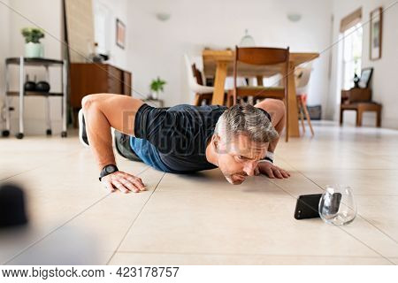 Mature man practicing pushups exercise while watching video on smartphone at home. Middle aged man doing plank workout at home while watching tutorial on mobile phone. Mid adult guy working out.