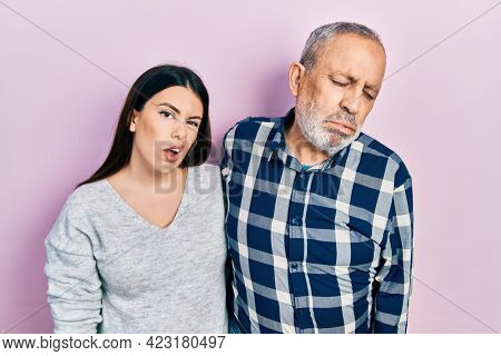 Hispanic father and daughter wearing casual clothes looking sleepy and tired, exhausted for fatigue and hangover, lazy eyes in the morning.