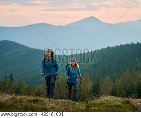 Two Persistent Professional Hikers With Trekking Poles And Backpacks Moving On Mountain Hills Agains