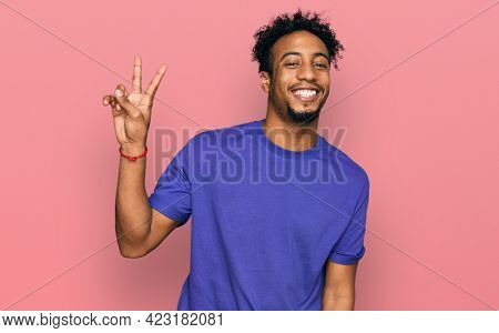 Young african american man with beard wearing casual purple t shirt smiling with happy face winking at the camera doing victory sign. number two.