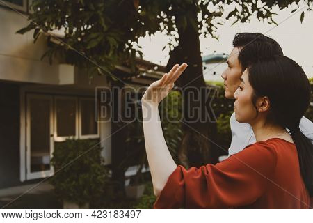Couple Sadly Standing In Front Of The House With Nostalgia, Look At The Old House And Remember The G