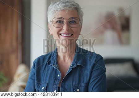portrait of a 55 year old smiling senior woman in her home