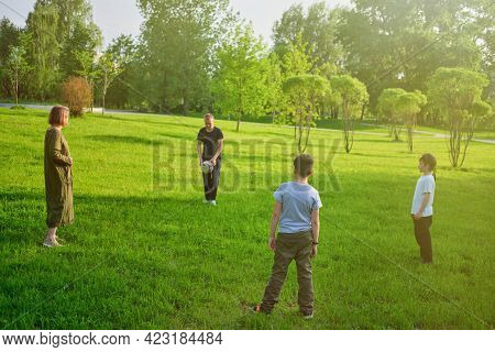 Four People In A Family Play With A Soccer Ball On A Sunny Evening