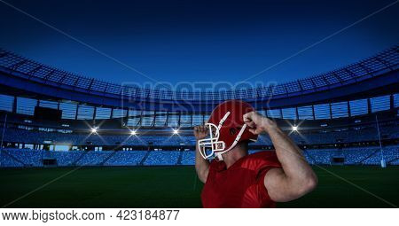 Caucasian male rugby player wearing helmet flexing his biceps against stadium in background. sports and fitness concept