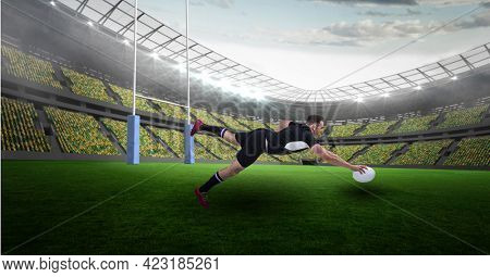 Caucasian male rugby player holding a rugby ball diving against stadium. sports, fitness and technology concept