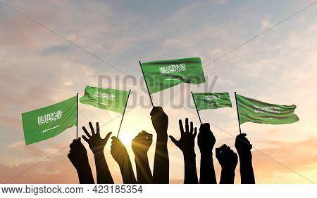 Silhouette Of Arms Raised Waving A Saudi Arabia Flag With Pride. 3d Rendering