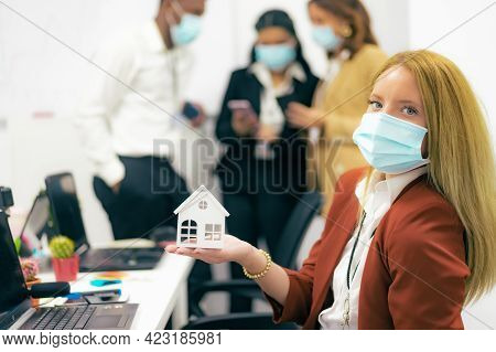 Young Woman With Protective Mask Showing White House In Office. Real Estate Agent And Coronavirus Co