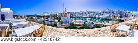 Greece travel. Cyclades, Paros island. Charming fishing village Naousa. view of old port with  boats and restaurants (taverns) by the sea. may 2021