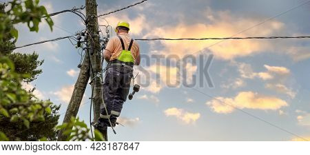 Electrical Lineman Working On Electric Pole. Electrician At Work. Banner Copy Space