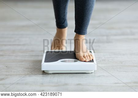 Unrecognizable Young Indian Woman Stepping On Scales To Measure Her Weight At Home, Closeup Of Feet