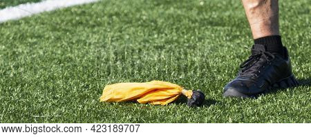 A Yellow Penalty Flag On A Green Turf Foot Next To The Officials Foot That Threw The Flag.