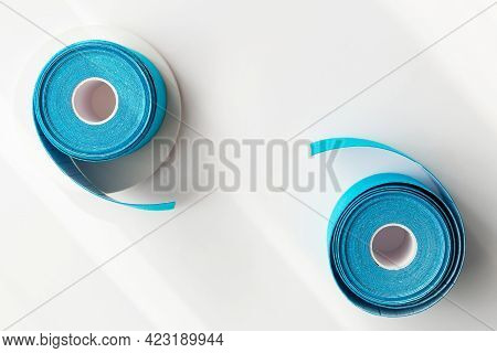 Two Blue Rolls Of Kinesiology Tape On White Background With Shadows And Podiums, Flat Lay. Recovery,