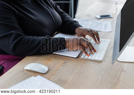Partial View Of African American Businesswoman Typing On Computer Keyboard In Office.