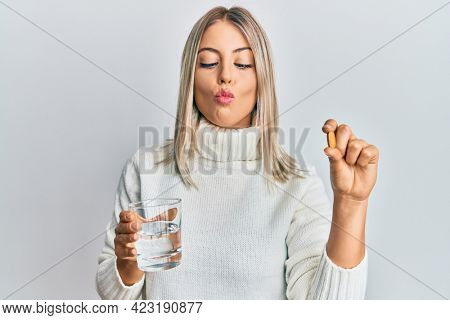 Beautiful blonde woman holding pill and glass of water making fish face with mouth and squinting eyes, crazy and comical.