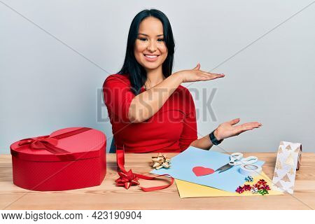 Beautiful hispanic woman with nose piercing doing handcraft creative decoration gesturing with hands showing big and large size sign, measure symbol. smiling looking at the camera. measuring concept.