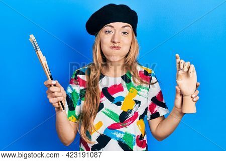 Young caucasian woman artist holding small wooden manikin and paintbrushes puffing cheeks with funny face. mouth inflated with air, catching air.