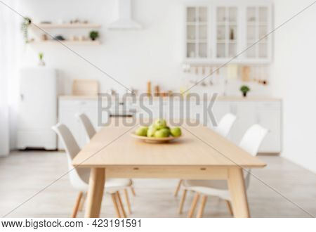 Blurred Background With Modern Light Kitchen, Wooden Dining Table And White Furniture, Chairs, Kitch