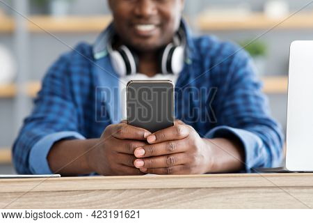 African American Man Using Brand New Smartphone, Checking Newest Mobile Application, Selective Focus