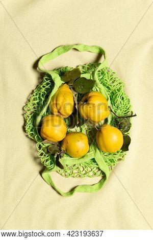 Few Organic Yellow Quince Apples With Leaves In Green Mesh Bag On Wrinkled Natural Pastel Colored Li
