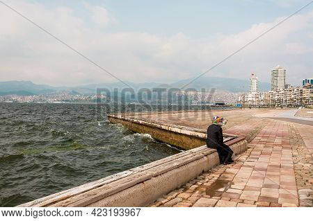 Woman Alone Siting On The Seashore, On The Embankment In The Old Turkish City Izmir. Landscape In Tu