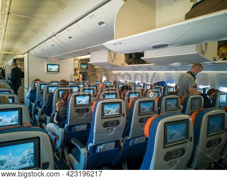 Moscow,russia-june 03,2021:aircraft Cabin Interior,passenger Seat With Monitor Screens.people In Med