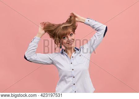 A Woman On A Pink Background Pulls Her Hair, A Middle-aged Girl In A Shirt Raises Her Hair With Her