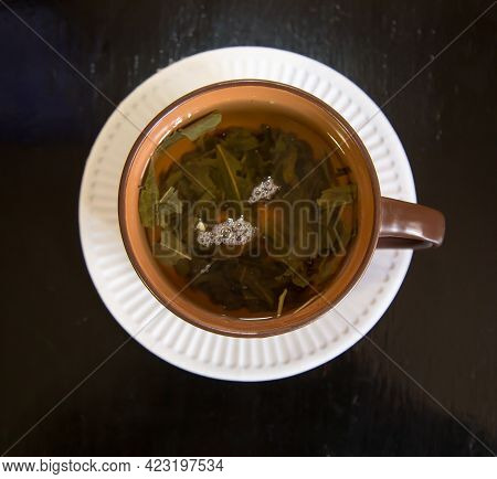 Top View Of A Cup Of Tea Brewed With Green Leaves With Air Bubbles On A Round White Plate With A Dar