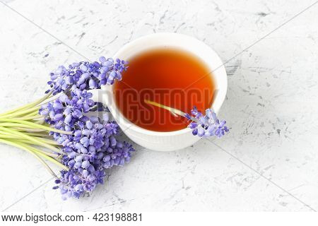 Lovely Postcard With Fresh Herbal Tea And Gentle Violet Flowers At The Background, Relaxing Teatime