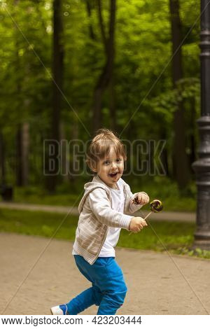 Cute Little Boy Holding A Large Round Lollipop On A Stick. Joyful Emotions. Sweets For Small Childre