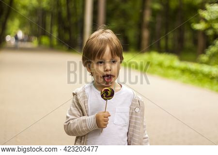 Portrait Of A Cute Little Boy Holding A Large Round Lollipop. The Baby Eats A Sweet, Big Lollipop.