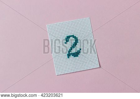 Green Number 2 Cross-stitch Embroidered On Piece Of Canvas In Center Of Pink Background. Hobby
