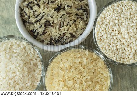 Different Types Of Rice. Wild Rice, Sushi Rice, Shredded And Steamed Rice On A Green Wooden Backgrou