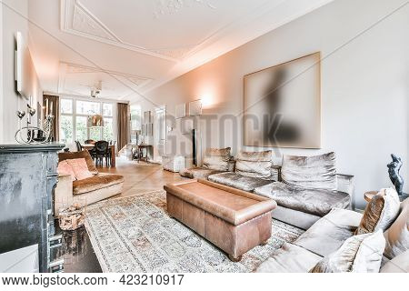 Interior Of Modern Living Room With Comfortable Sofas And Armchairs Placed On Parquet Floor With Rug
