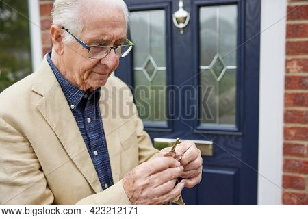 Confused Senior Man With Early Stage Dementia Trying To Find Correct Door Key Outside House