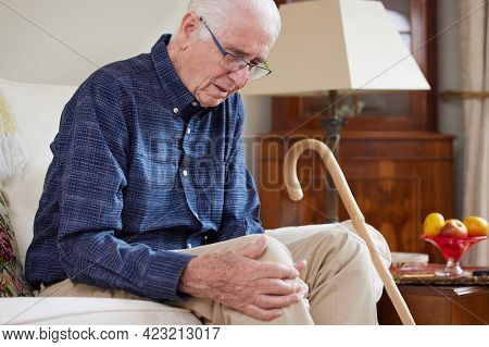 Senior Man Sitting On Sofa At Home Suffering With Knee Pain From Arthritis