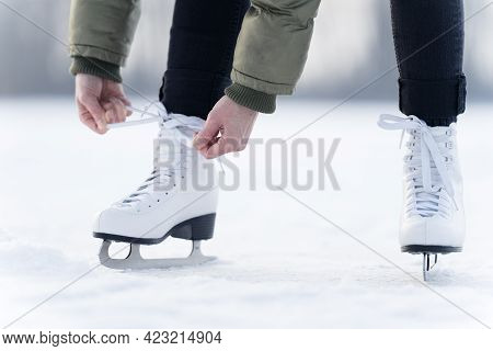 Tying The Laces Of Winter Skates On A Frozen Lake, Ice Skating