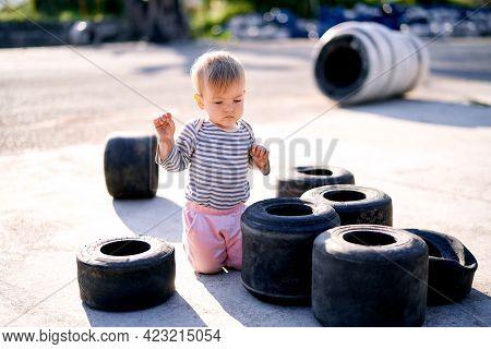 Child Kneels On The Asphalt Near A Pile Of Small Car Tires