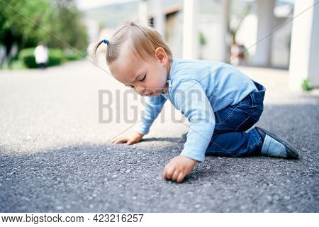 Little Girl With A Ponytail Sits On Her Knees On The Road In The Park